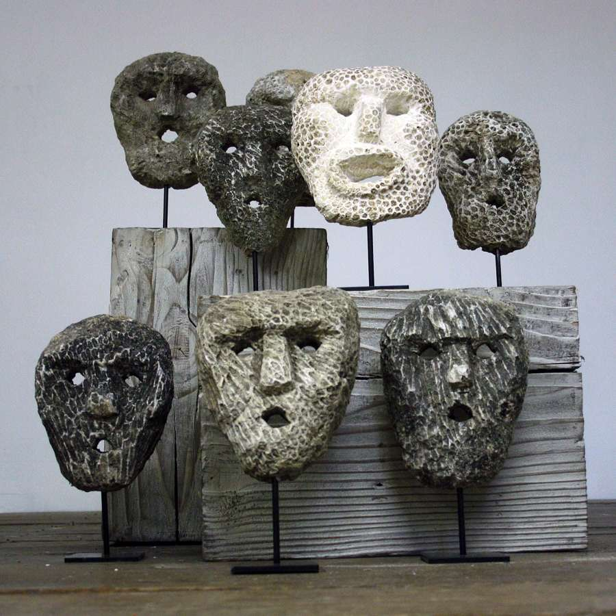 Collection of Fossillized carved coral animist Masks on stand